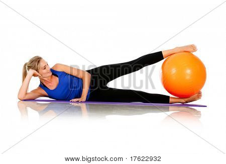 Sportive woman exercising with a Swiss ball - isolated