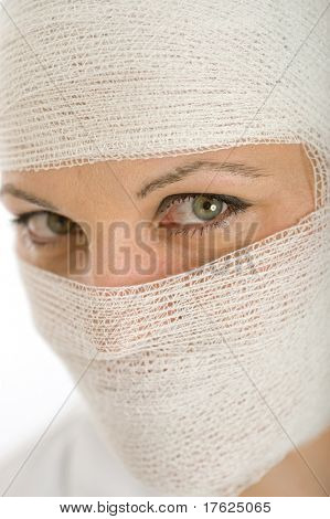 Close-up portrait of a woman with a bandaged head and face