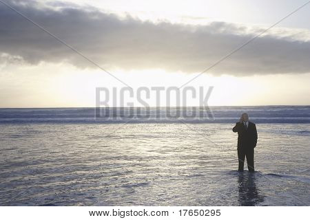 Business man using mobile phone standing in sea at sunset, elevated view