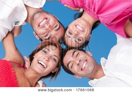 Happy smiling friends with their heads together looking at camera in a sunny day