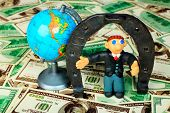 Shot of a plasticine businessman in a suit. Over money background.