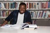 Happy African Male Student With Laptop In Library poster