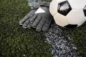 sport, soccer and game - ball and goalkeeper gloves on football field poster