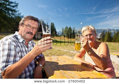 Happy retired couple drinking beer after a long hike