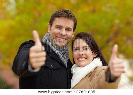 Happy sonriente pareja en otoño sosteniendo sus pulgares