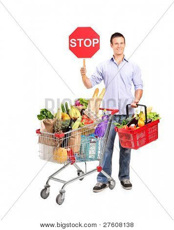 Full length portrait of a man holding a shopping basket and a stop sign isolated on white background