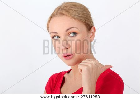 Blond woman in red shirt designating something with thumb up