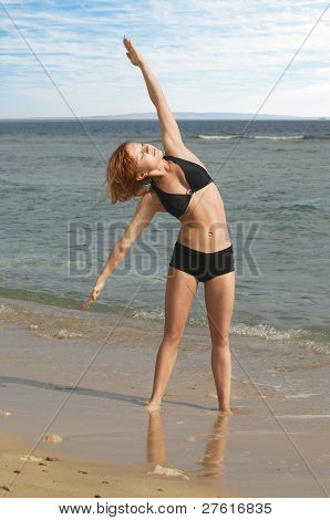 Beautiful red woman exercising at the beach