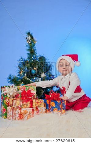 Charming baby (boy) in Santa Claus suit, sitting beside a Christmas tree decorated and gifts. He hol