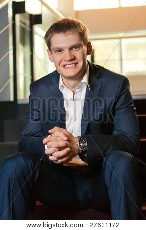 Young Businessman Sitting On Stairs Looking At Camera