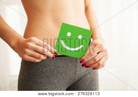 poster of Women Health. Closeup Of Healthy Female With Beautiful Fit Slim Body In Black Panties Holding Green