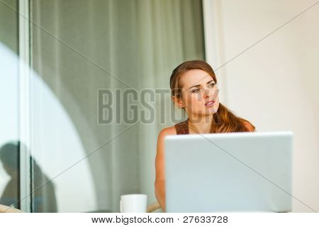 Portrait Of Thoughtful Beautiful Woman Working On Laptop