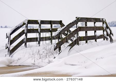 Fence with snow in the countryside of the Netherlands