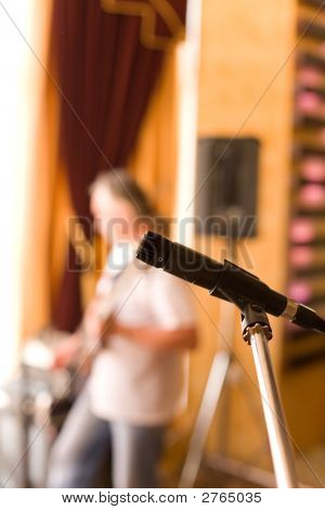 Microphone On Tripod With Guitarist On Background