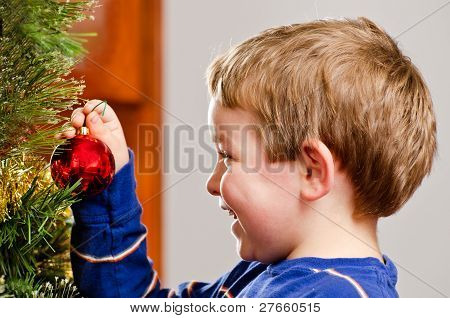 Young boy decorates Christmas Tree for holiday.