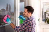 Handsome Young Man Cleaning Windows With Cloth And Spray Bottle At Home poster