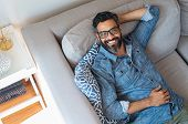 Happy mature man with eyewear and beard relaxing on sofa at home. Handsome latin man with hands behi poster