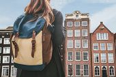 Tourist Girl Or Student With Backpack Looks At The Traditional Houses In Amsterdam In The Netherland poster