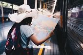 Young Woman Traveler Holding Map While Looking For Some Direction At Train Station For Travel. Trave poster