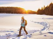 Winter sport woman hiking in snowshoes. Snowshoeing girl in the snow with shoe equipment for outdoor poster