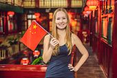Enjoying Vacation In China. Young Woman With A Chinese Flag On A Chinese Background. Travel To China poster