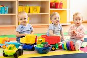 Group Of Babies Is Playing On Floor In Nursery Or Creche. Children In The Day Care Center. Fun In Th poster