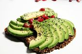 Sliced Avocado And Ripe Pomegranates On Toast Bread With Spices And Avocado poster