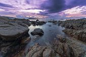 Long Exposure Image Of Dramatic Sky And Wave Seascape With Rock In Sunset Scenery Background. poster