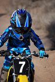pic of moto-x  - Vertical image of a young boy motor cross racer riding a yellow dirt bike in the desert - JPG