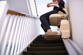 Detail Of Senior Woman Sitting On Stair Lift At Home To Help Mobility poster