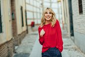 Happy Young Blond Woman Walking Down The Street. Smiling Blonde Girl With Red Shirt Standing Outdoor poster