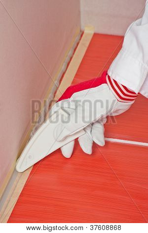 Worker With Tool Smooth Silicone Sealant On Corner With Tiles