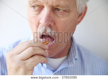 man taking fish oil pill