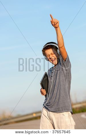 Boy Feeling Free With Headphones And Tablet.
