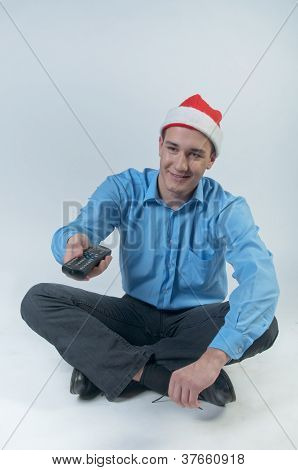 A man with a television remote control watching Christmas TV