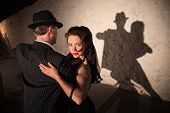 image of tango  - Two tango dancers performing under spotlight indoors - JPG