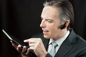 Businessman Wearing Headset Using Tablet