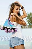 stock photo of roller-derby  - Photograph of a roller derby sexy woman holding her skates by the laces outdoors - JPG