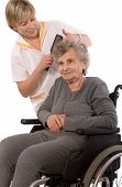 stock photo of crippled  - Nurse dressing the hair of a senior woman - JPG