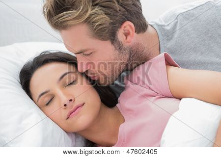 Man kissing his sleeping wife on the cheek in bed