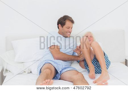Father tickling son on the bed