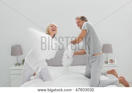 Fun couple having a pillow fight at home in bedroom