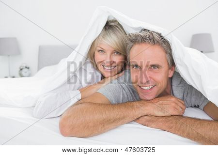 Happy couple smiling under the covers at the camera at home in bed
