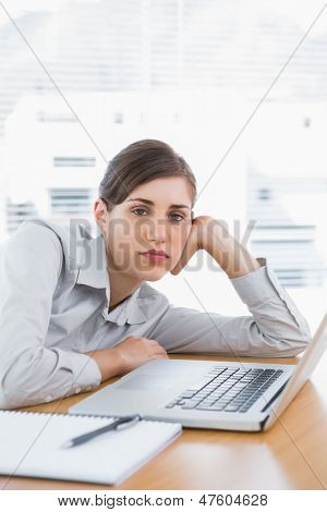 Fed up businesswoman looking at camera at her desk