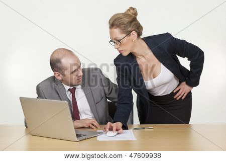 Businessman Ogling The Cleavage Of His Coworker