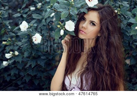 Beautiful Woman With Curly Long Hair. Outdoors Portrait On Garden Background, Summer Nature.