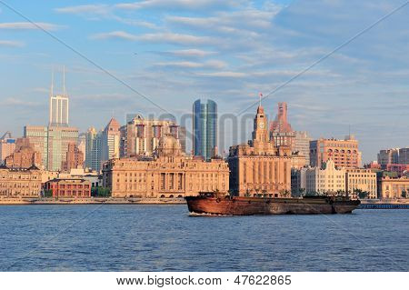 Shanghai historic and urban buildings over Huangpu River in the morning with blue sky and boat.