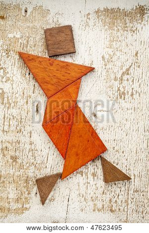abstract figure of a female dancer built from seven tangram wooden pieces, a traditional Chinese puzzle game; rough white painted barn wood background