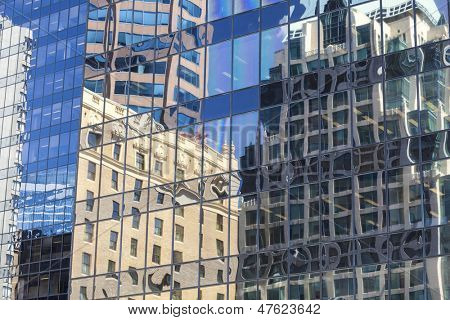 Reflections of old buildings in the windows of modern city office building tower