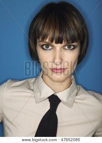 Closeup portrait of a bobbed haired young woman wearing tie against blue background